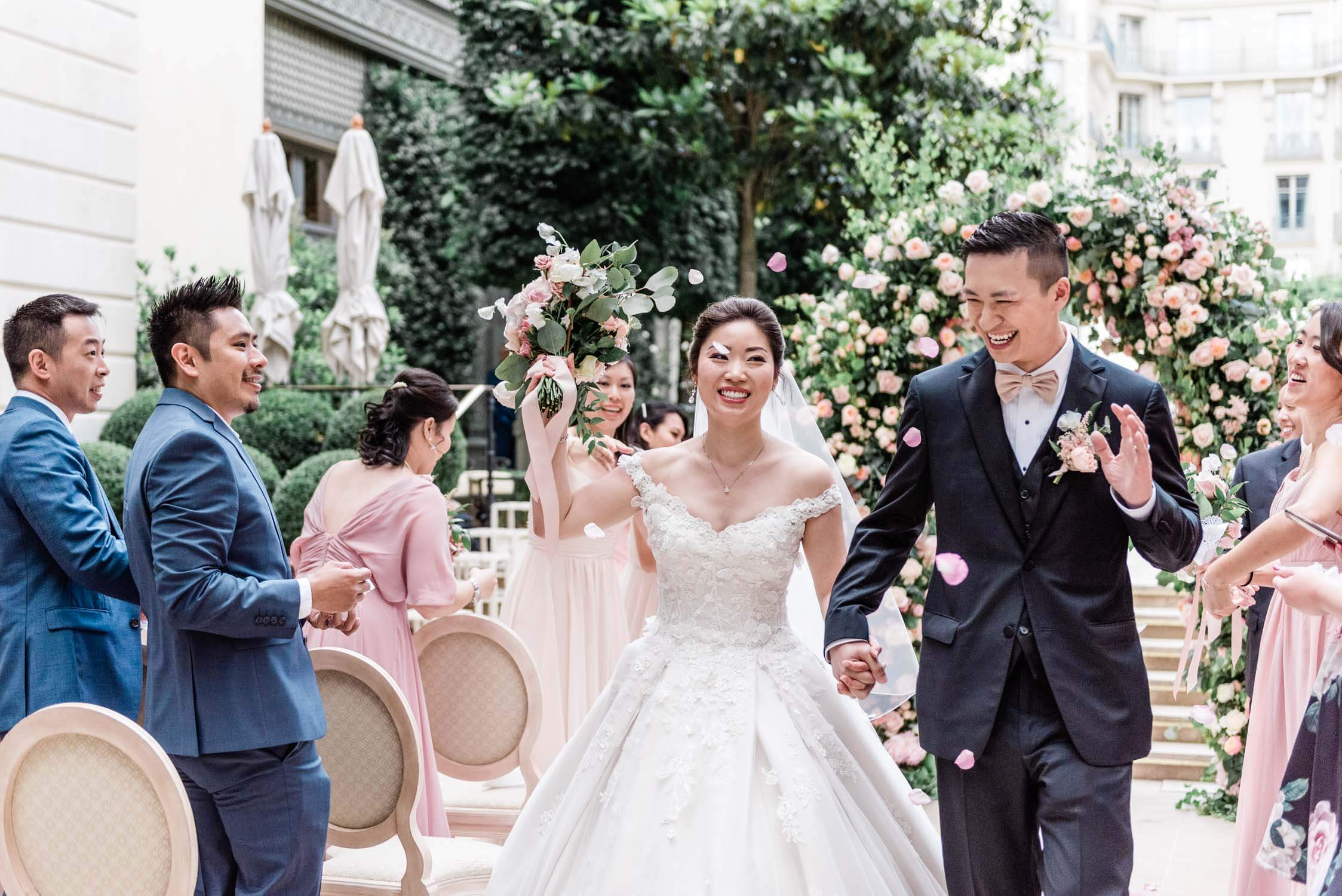 A bride and groom walk out of their elopement ceremony in Paris, being showered by rose petals