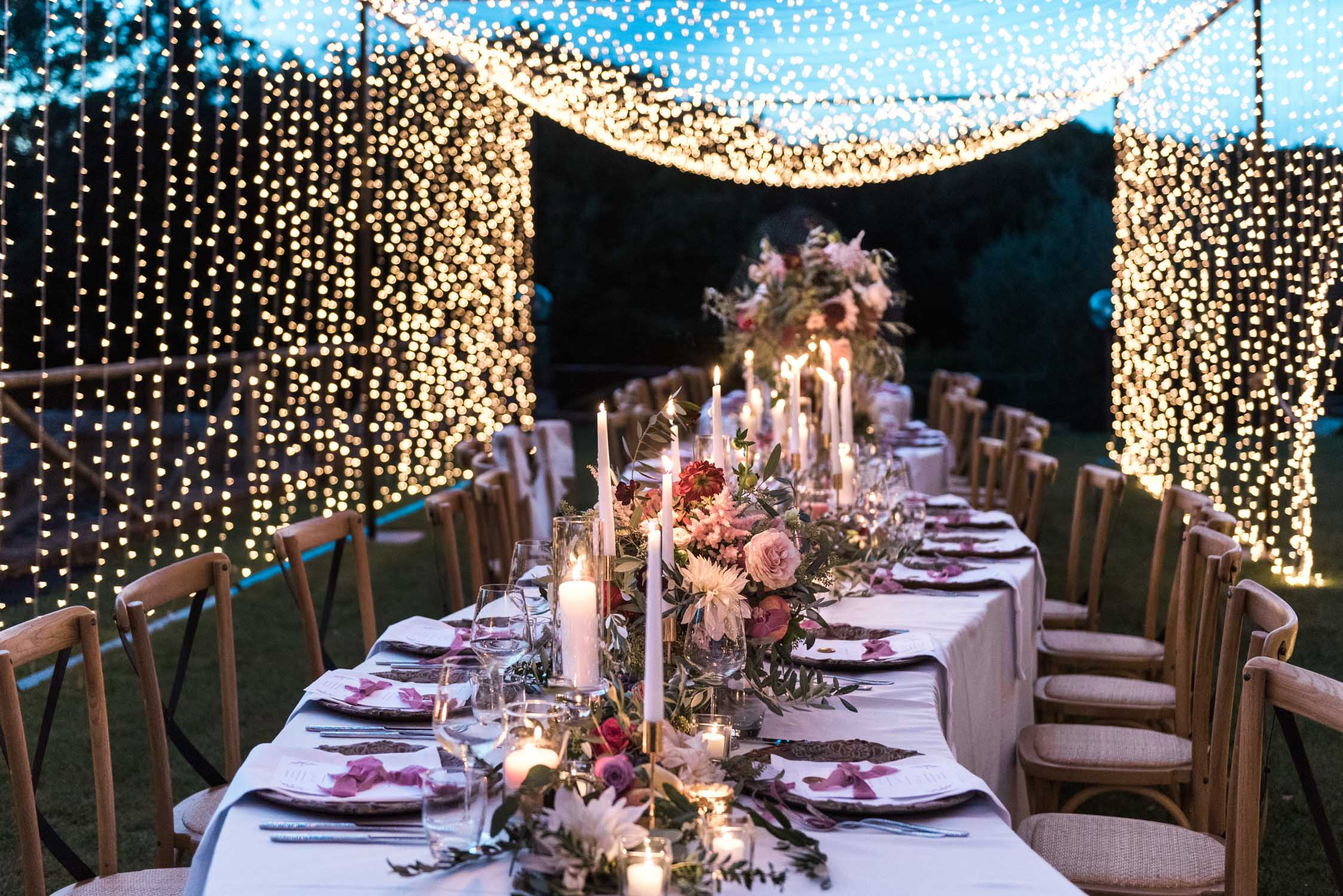 Flower abundant S shaped wedding table setting in a tunnel of light in Siena, Tuscany, Italy